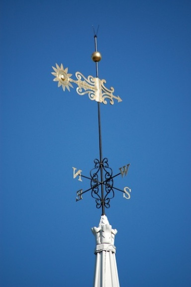 gold weathervane on white church steeple