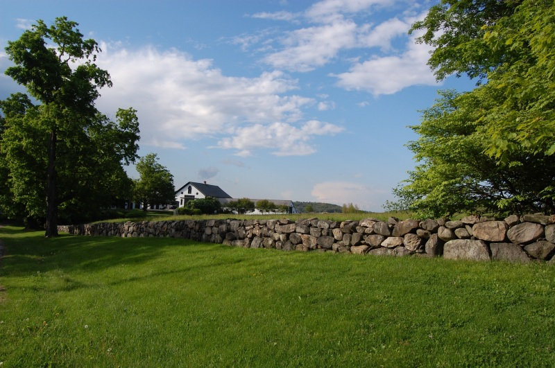 stone wall in front of white barn and blue sky overhead