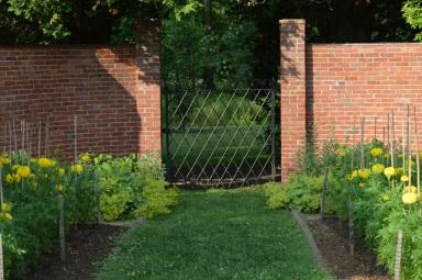 wrought iron gate in brick wall into secret garden perhaps